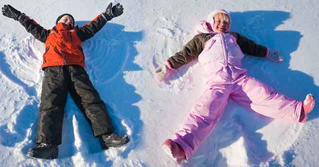 Two kids making snow angels